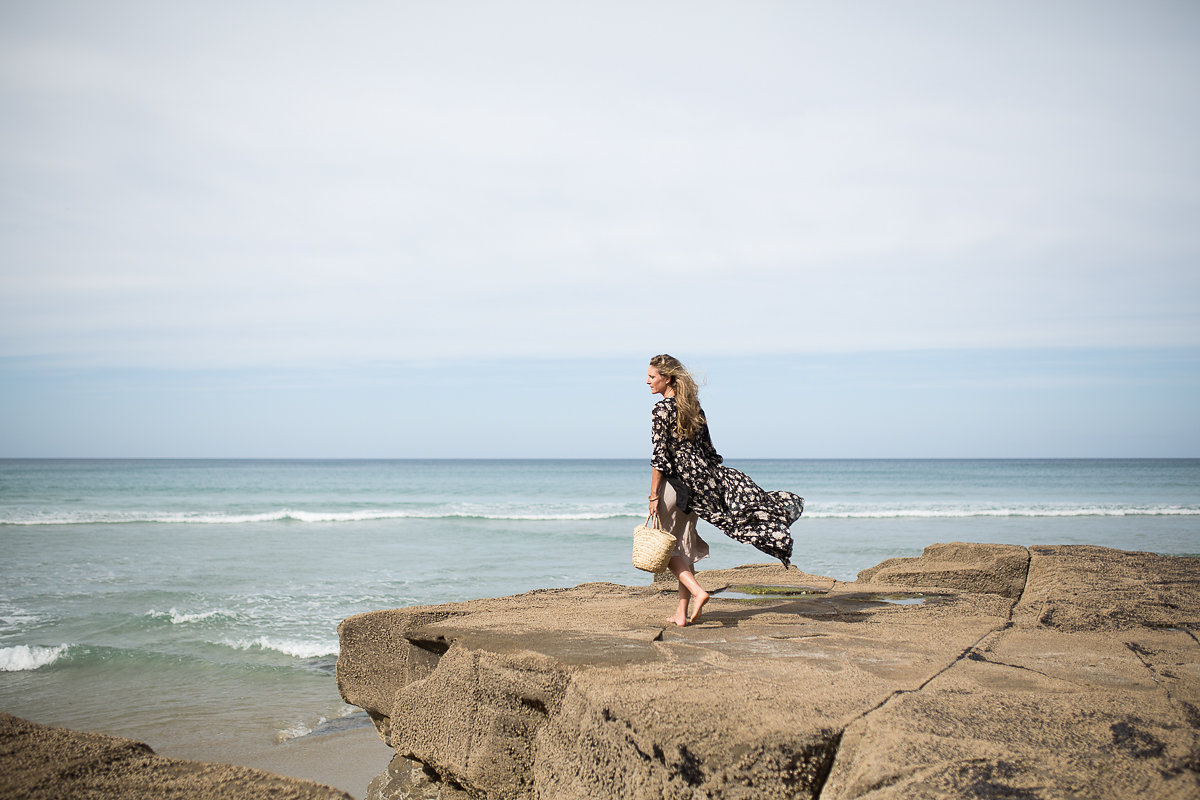 Wild delicious Gallery image Amber walking along the cliffside of a beach