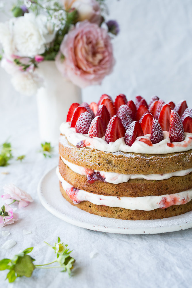 pistachio and strawberry cake on a plate with 3 layers of cream and jam with fresh strawberries on the top. A vase of flowers sits behind the cake.