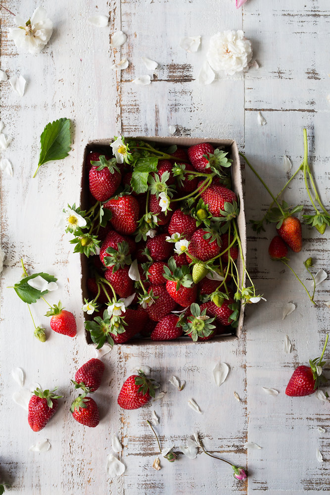 strawberries in a cardboard box on white wood table.