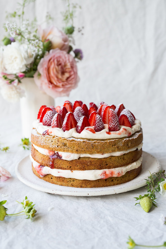 3 tiered cake with strawberries and a vase of flowers